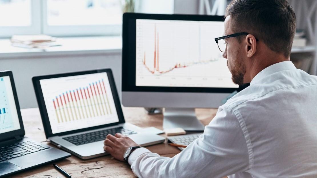 Pracownik obserwujący statystyki na komputerach